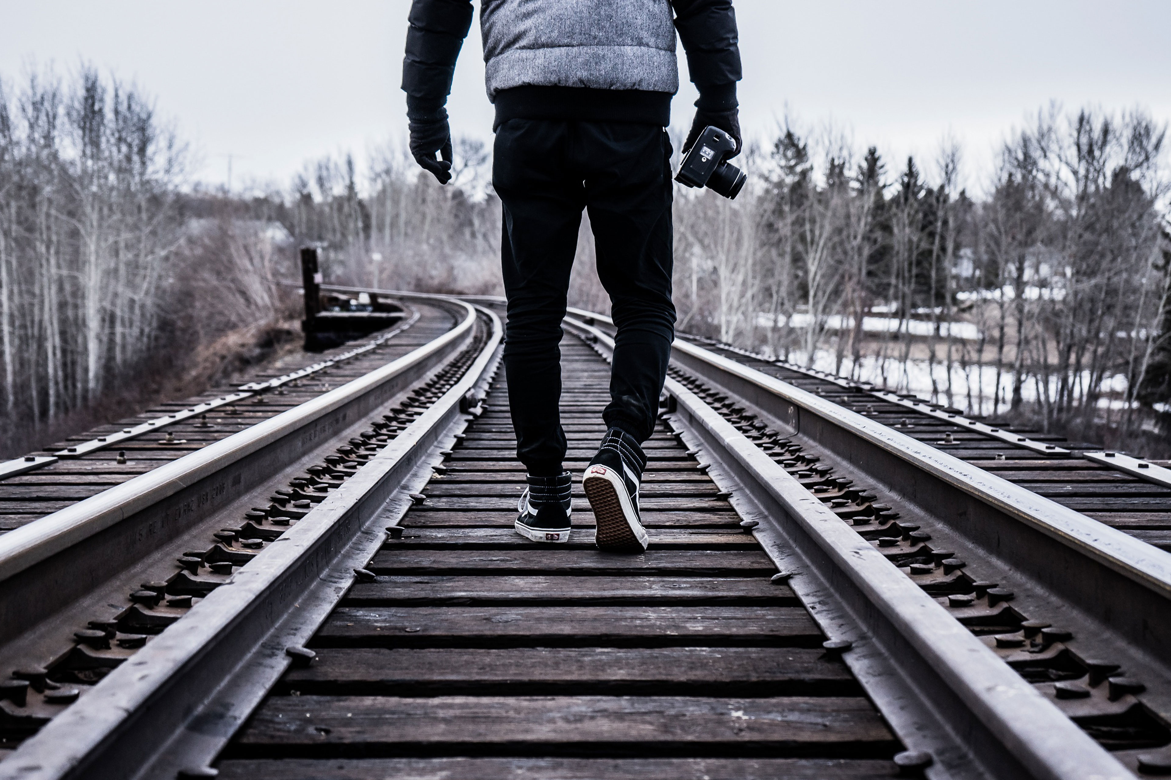 Guy walking on train tracks
