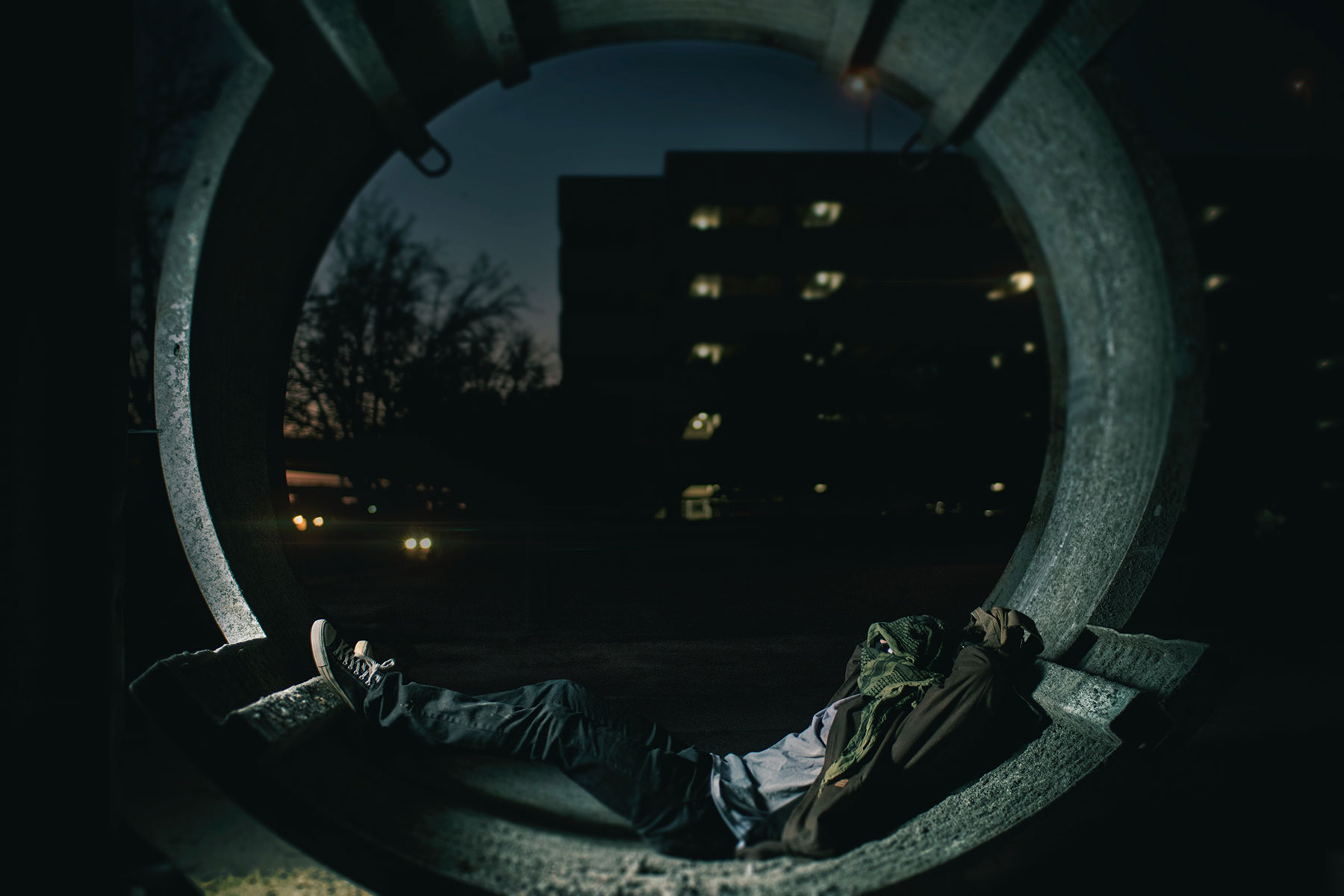 Person sleeping in a piece of a concrete tunnel